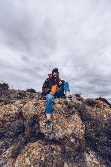 D'en bas femme positive regardant à la caméra et assis sur des rochers au bord de la falaise avec vue pittoresque — Photo de stock