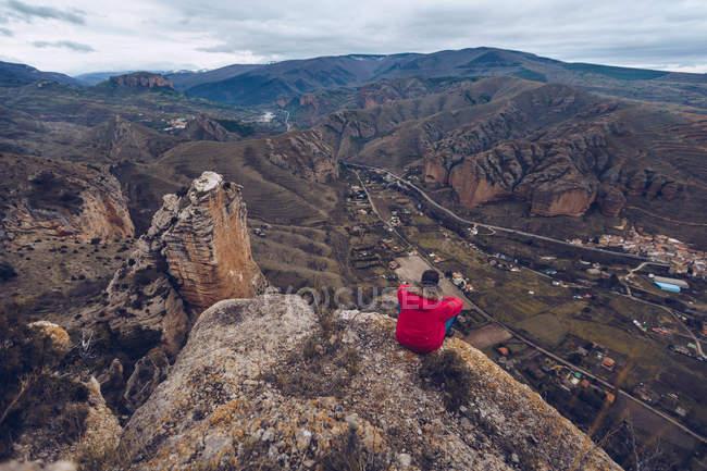 Por trás vista de homem irreconhecível em casaco olhando e sentado no topo da montanha — Fotografia de Stock