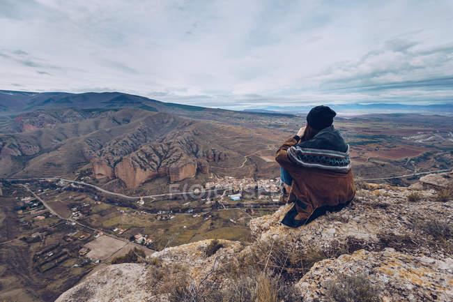 Vue arrière d'une femme méconnaissable assise sur des rochers au bord d'une falaise avec vue pittoresque — Photo de stock