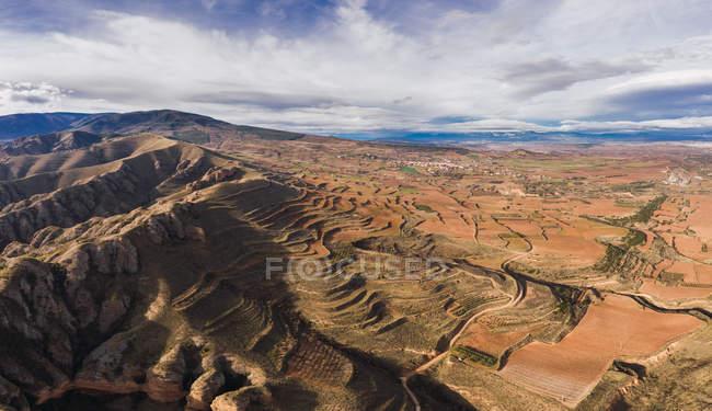 Величний гірський ланцюг з різнокольоровими схилами та яскравим небом з хмарами. — стокове фото