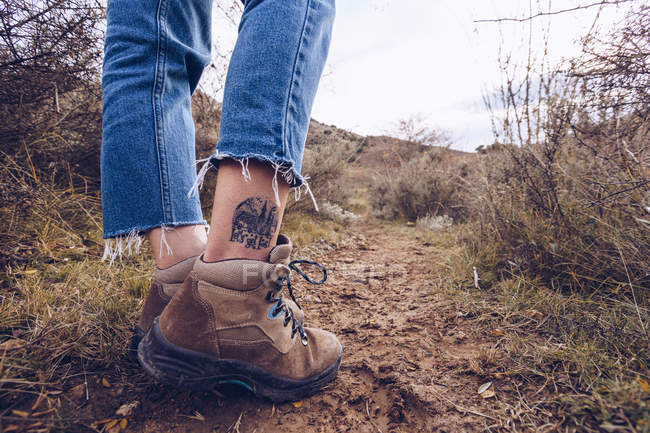 Legs of tattooed hiker in boots and jeans walking along muddy pathway at autumn field with dried grass — стокове фото