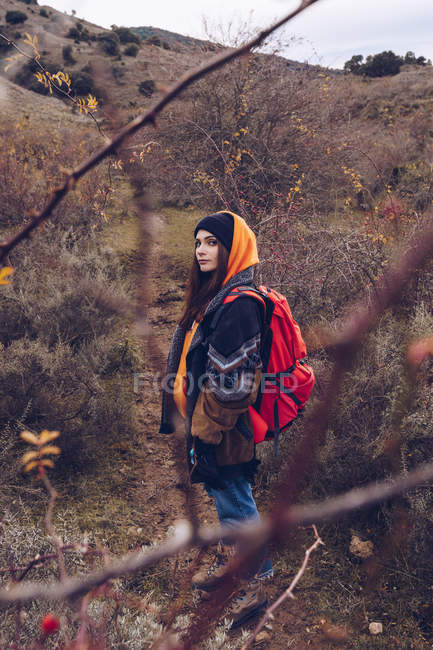 Young woman with bright backpack in warm clothes walking along road with dried leaves by bare trees — Stock Photo