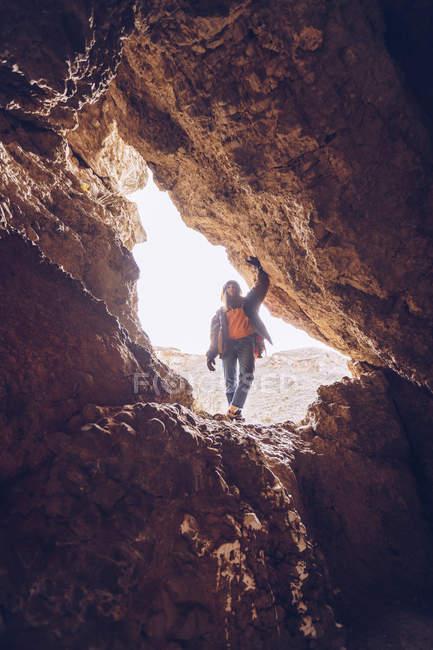 Обережна жінка в теплому одязі, що стоїть біля кам