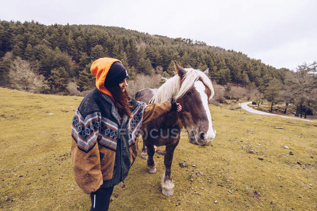Loving woman in warm clothes stroking peaceful horse while standing at rural meadow by forest — Stock Photo