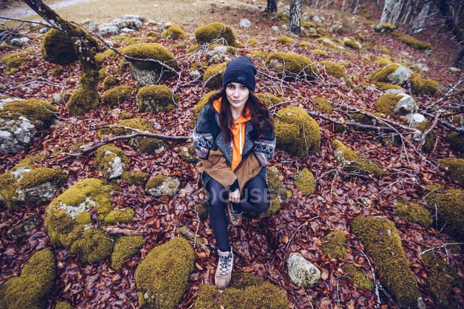 Зверху жінка в капелюсі сидить в каміннях, оточених сухим листям і мохом, і дивиться в камеру. — стокове фото