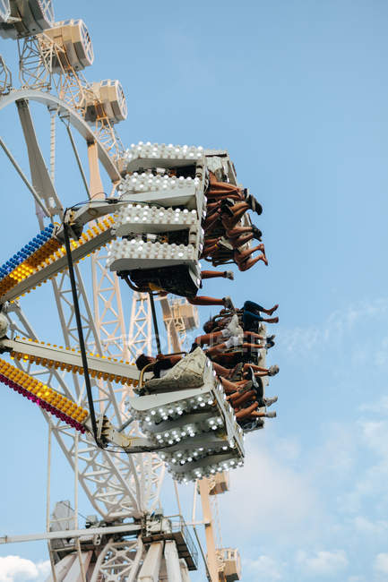 From below of visitors entertaining at modern dangerous spinning carousel in summer amusement park — Photo de stock