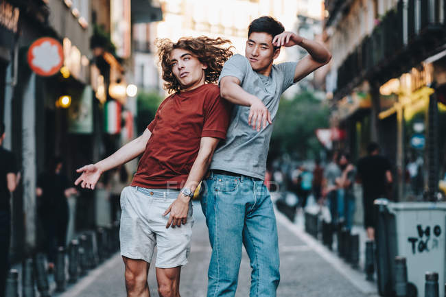 Side view of excited multiracial men jumping together and slamming back on city street — Photo de stock