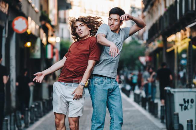 Вид сбоку возбужденных мультирасовых мужчин, прыгающих вместе и мчащихся назад по городской улице — стоковое фото