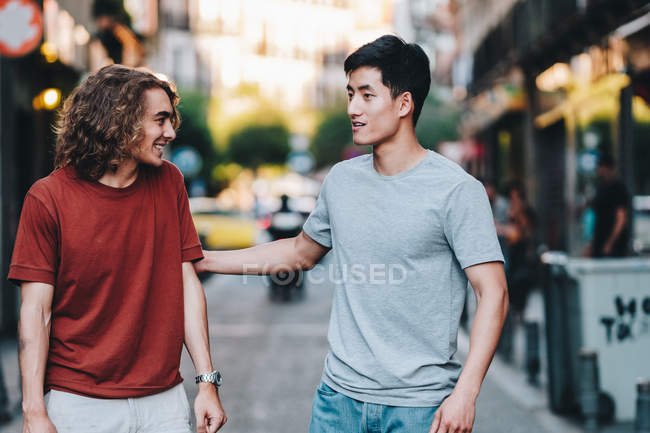 Carefree interested multiethnic men in casual clothes talking while strolling along city street — Stock Photo
