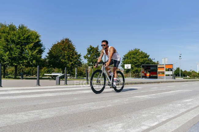 Athletic man in sunglasses wearing white shirt and black shorts riding bike on city roadway with green trees on roadside — Stock Photo