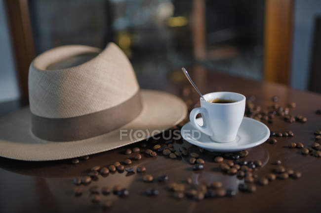 Ceramic cup with teaspoon among roasted coffee beans beside hat on wooden table — Stock Photo