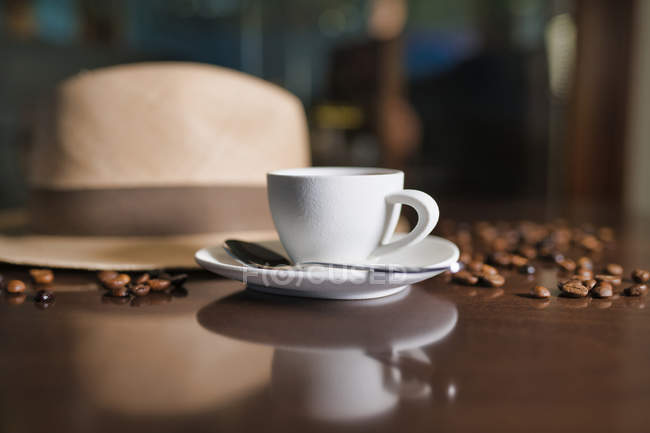 Ceramic cup with teaspoon among roasted coffee beans beside hat on wooden table — стокове фото