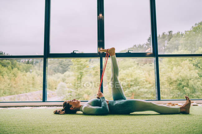 Side view of barefoot slim woman in sportswear performing exercise with rubber band on leg while lying on floor in gym during training — Stock Photo