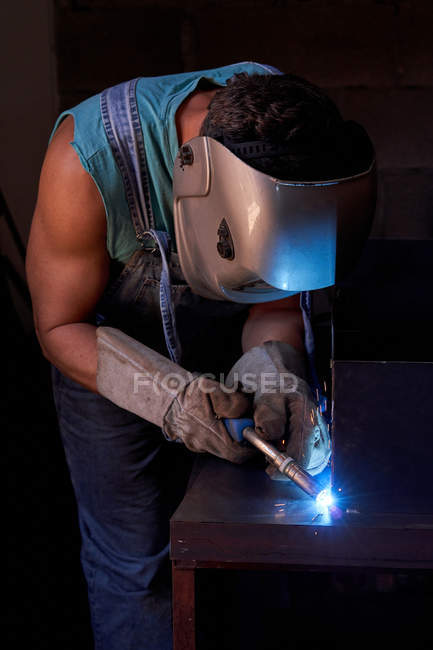 Side view of craftsman in protective face mask wearing overalls and gloves working in workshop and soldering metal construction — Stock Photo