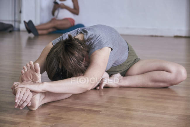 Розслаблена жінка, що сиділа на передньому плані під час тренування йоги в просторий студії — стокове фото