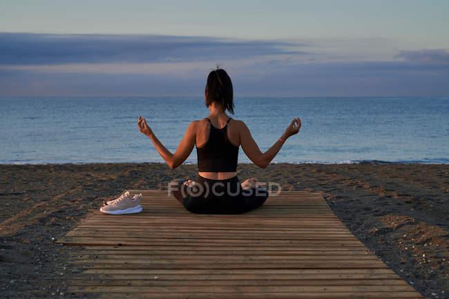 Femme positive avec les jambes croisées assis sur le bord de la mer contre ciel nuageux en soirée — Photo de stock