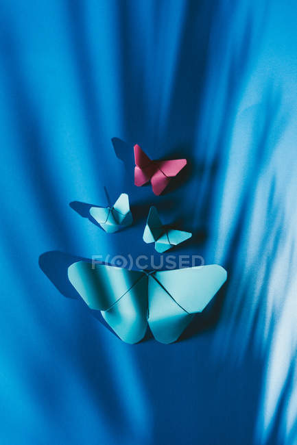 Fragile butterflies made of paper attached to blue silk fabric — Stock Photo