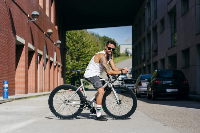 Sportive man in sunglasses wearing white sleeveless shirt and black shorts sitting on bicycle between buildings — Stock Photo