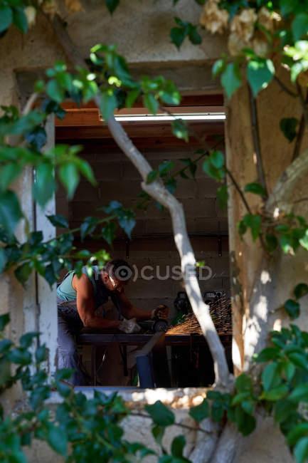 Ansichten von Baumzweigblättern eines Arbeiters in Schutzbrille und Handschuhen beim Schneiden von Metall mit einem Schleifer mit Funkenflug während der Arbeit in der Werkstatt — Stockfoto