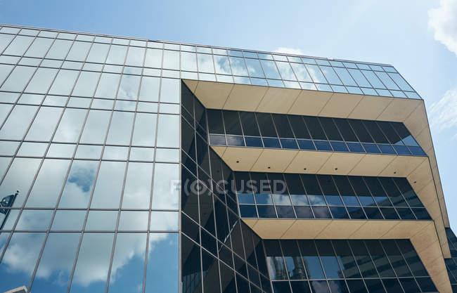 Знизу - дивовижна геометрична складна споруда з великими вікнами, які відбивають білі хмари в небі Техасу. — стокове фото