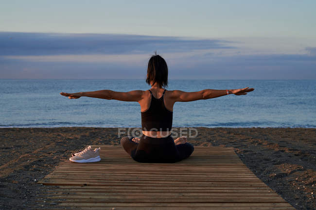 Back view of fit female in sportswear with outstretched arms sitting crossed legged near sea and doing yoga in evening — Stock Photo