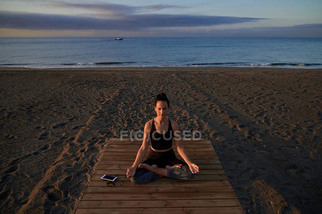 Barefoot female in sportswear sitting in lotus pose and meditating during yoga training on beach — Stock Photo