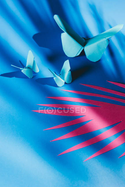 Fragile butterflies made of paper with palm tree print shadow attached to blue silk fabric — Stock Photo