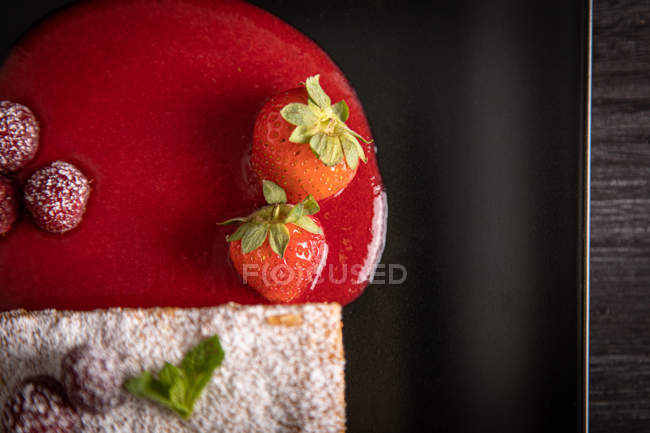 Diphlomate cream and red fruit strudel in elegant black plate — Stock Photo