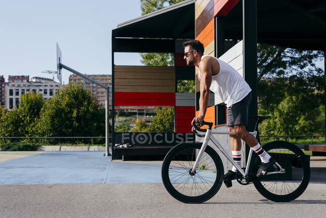Sportive man in sunglasses wearing white sleeveless shirt and black shorts standing while riding a bicycle between buildings — Stock Photo