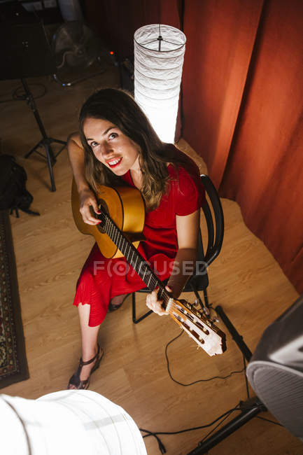 From above talented woman in red dress performing song and playing guitar in warm lighted stage nearby white lamp — Stock Photo