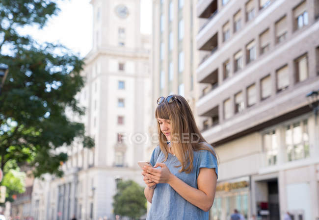 Blonde young cheerful female with sunglasses standing on street of city and typing message on smartphone — Stock Photo
