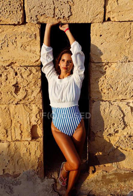 Мирная загорелая женщина-путешественница в стильном полосатом купальнике и белой блузке стоя и поднимая руки в качающихся дверях — стоковое фото