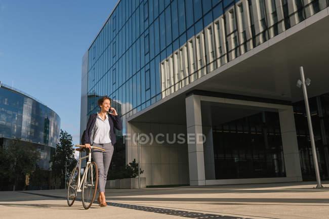 Предпринимательница с велосипедом улыбается и говорит по смартфону во время прогулки возле современного здания — стоковое фото