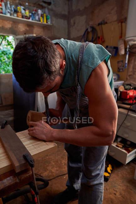 Seitenansicht des Arbeiters mit Holzhammer beim Arbeiten mit Holzplanke in kleiner Werkstatt — Stockfoto