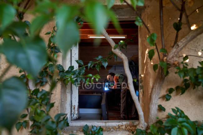 Ansichten von Baumzweigen eines professionellen Meisters in Schutzmaske beim Löten von Metall während der Arbeit in einer kleinen Werkstatt — Stockfoto
