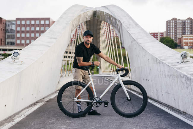 Happy adult bearded man in black cap wearing black shirt and beige shorts standing with bike across footbridge in city looking at camera — Stock Photo