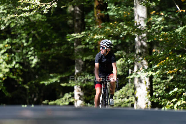 Professional cyclist riding bike in park — Stock Photo