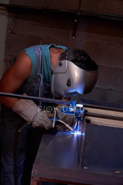 Seitenansicht des Handwerkers in Schutzmaske mit Overalls und Handschuhen bei der Arbeit in der Werkstatt und beim Löten von Metall — Stockfoto