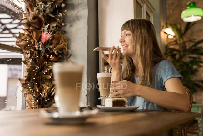 Блондинка счастливая молодая женщина с челкой улыбается и разговаривает по смартфону, держа чашку кофе в уютном кафе — стоковое фото