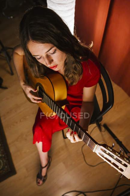 Von oben talentierte Frau in rotem Kleid singt und spielt Gitarre in warm beleuchteter Bühne neben weißer Lampe — Stockfoto