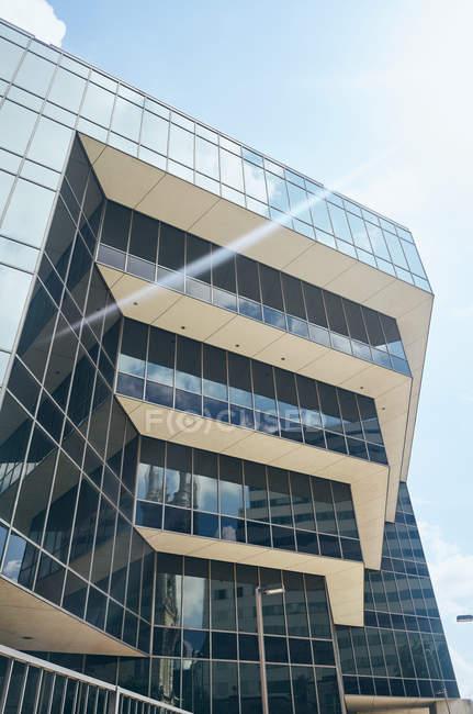 Von unten erstaunliche geometrische komplexe Struktur mit großen Fenstern, die weiße Wolken in Himmelstexas reflektieren — Stockfoto