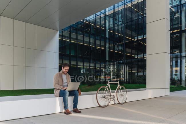 Happy man manager souriant et naviguant ordinateur portable assis à l'extérieur près de vélo sur un bâtiment contemporain dans la rue de la ville — Photo de stock