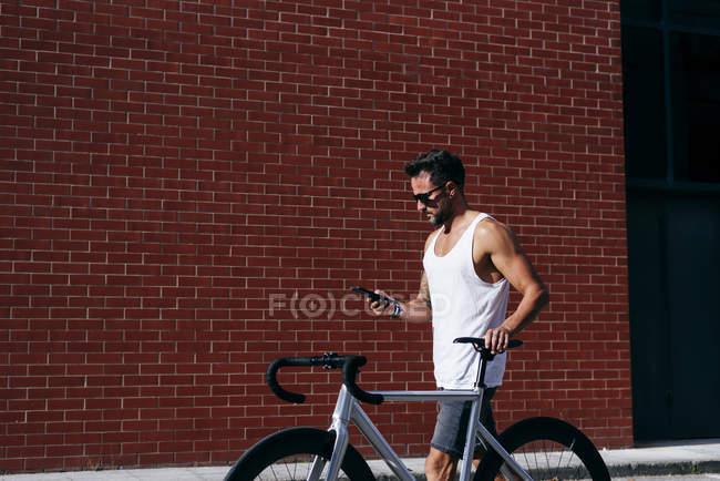 Vue latérale du beau cycliste masculin en vêtements de sport et lunettes de soleil à l'aide d'un smartphone tout en restant debout avec un vélo à côté du mur de briques rouges — Photo de stock