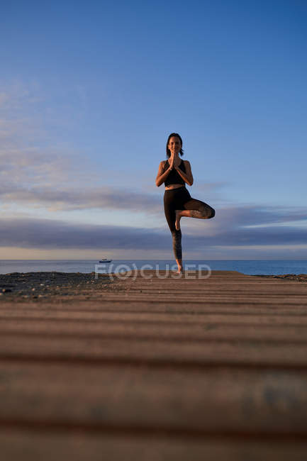 Happy slim female in sportswear standing in tree pose on sandy beach near waving sea in evening — Stock Photo