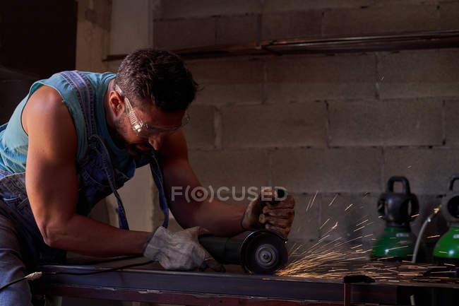 Seitenansicht des Arbeiters mit Schutzbrille und Handschuhen beim Schneiden von Metall mit einem Schleifer mit Funkenflug während der Arbeit in der Werkstatt — Stockfoto