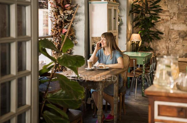Blonde jolie jeune fille avec des bangs souriant et parlant sur smartphone dans un café douillet — Photo de stock
