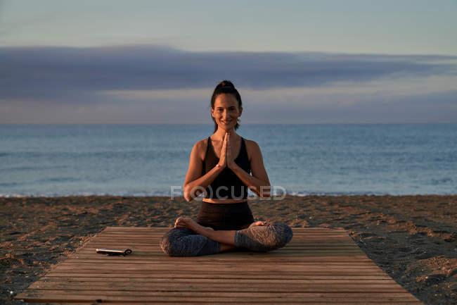 Positive female with crossed legs and clasped hands smiling and meditating while sitting on seashore in evening — Stock Photo