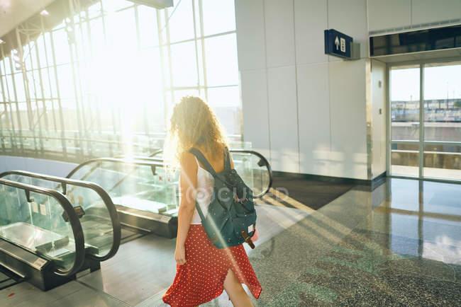 Vista laterale di affascinante donna riccia in gonna rossa con zaino a piedi giù alla scala mobile in aeroporto in Texas — Foto stock