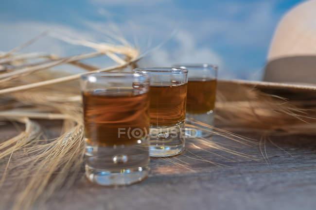 Виски со шляпой и пшеницей на деревенском столе — стоковое фото