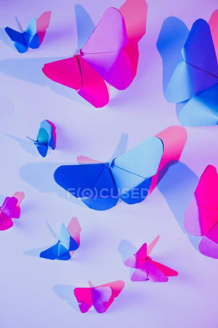 Borboletas rosa e azul ligadas à parede lilás — Fotografia de Stock